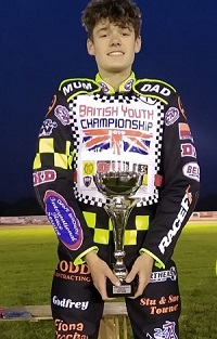 Sam: young man wearing speedway jumpsuit smiling holding an award