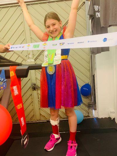 Chloe: young girl wearing a superhero outfit and a medal