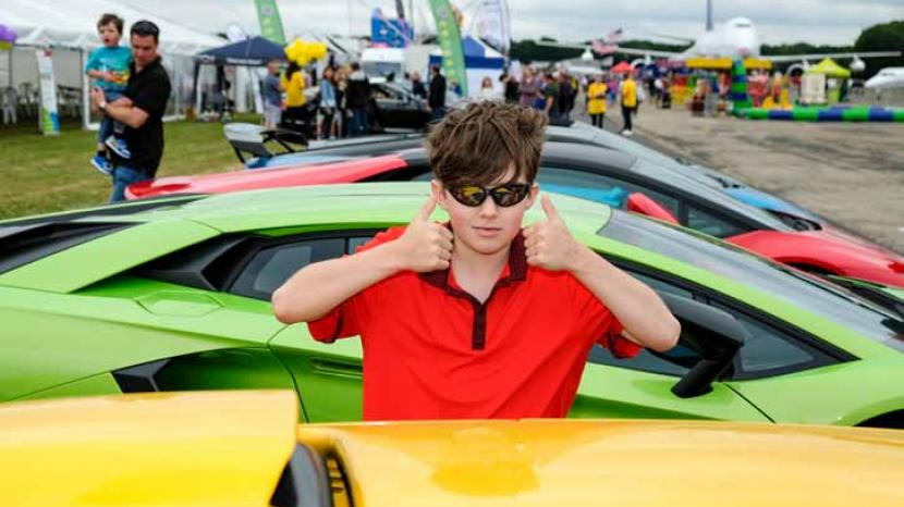 "A child giving the camera a ""thumbs up"" at the Supercar Event"